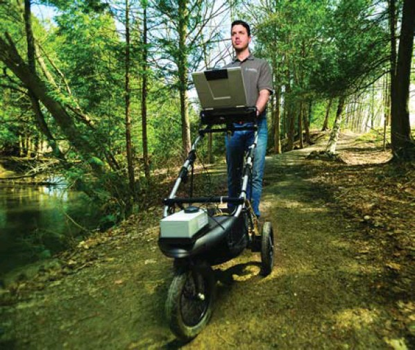TRCA's Adam Dembe uses a High Efficiency Trail Assessment Process device to collect detailed data on conservation authority-managed trails to assess the accessibility of conservation trails. Photo by Shayne Gray.